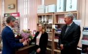 Burmistrz wręcza naczelnik poczty bukiet kwiatów